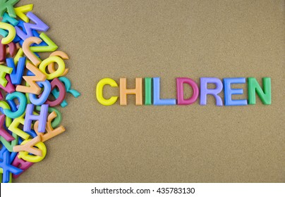 """The colorful word """"WORDS"""" next to a pile of other letters over the brown board surface composition."""