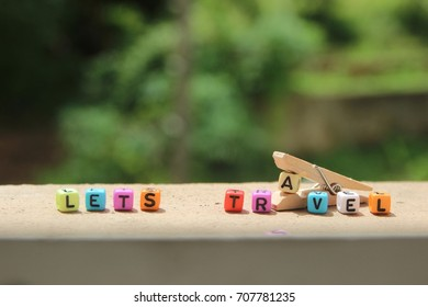 "Colorful wording ""LETS TRAVEL"" with wooden peg isolated with blurred background."