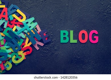 """The colorful words """"BLOG"""" made with wooden letters next to a pile of other letters over dark background."""