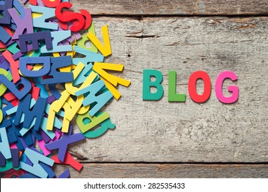 "The colorful words ""BLOG"" made with wooden letters next to a pile of other letters over old wooden board."