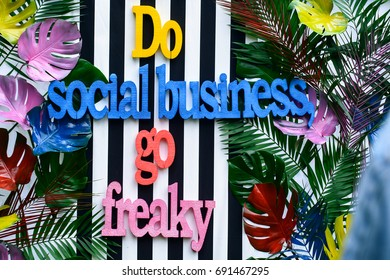 colorful words do social business written in tropical leaves background