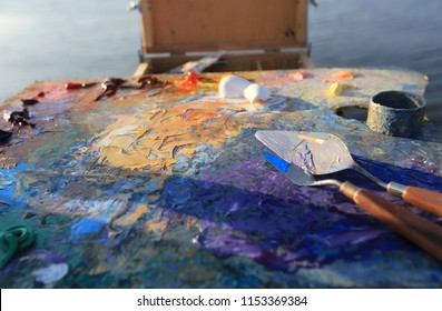 Colorful workplace of the artist with brushes and oil paints in the open air