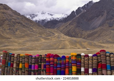 Colorful woven fabrics contrasted against stark alpine landscape at Abra La Raya pass, 4338 meters, on the road from Cusco to Puno, Peru
