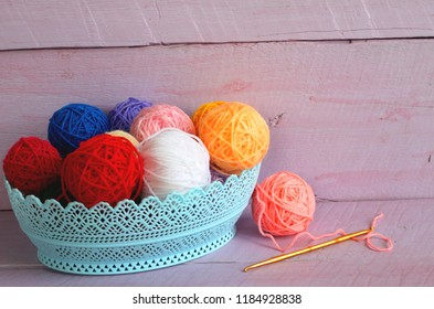 Colorful yarn balls in blue basket for knitting isolated on a pink background.