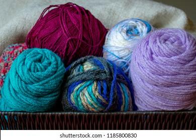 Colorful yarn skeins for knitting or crochet inside wicker basket