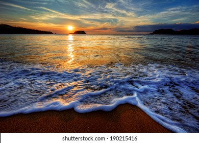 Colorful yellow and blue ocean bay sunset with sea foam