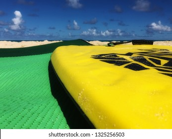 Colorful yellow boogie board on a green mat on the sand under a blue sky at the beach