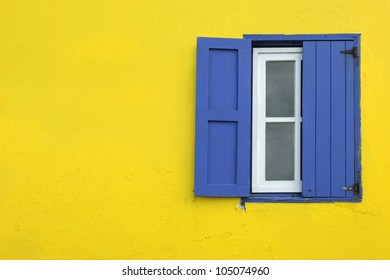 Colorful yellow house with blue shutters and window in Governor's Harbour, Eleuthera, Bahamas, Caribbean