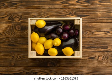 Colorful yellow lemons and purple aubergine packed together in a small wooden crate wooden table at an organic farmers market viewed from above centered on a wooden table