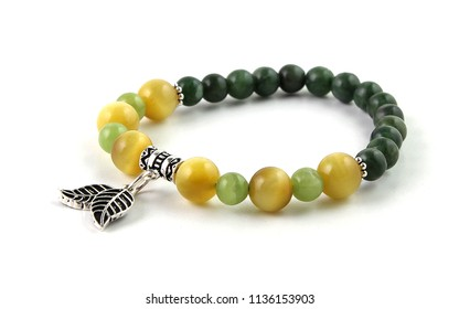 Colorful young girl bracelet isolated on white with green prehnite, yellow cat's eye tiger's eye and dark green canadian jade stones and silver leaf figures at middle