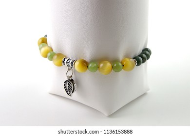 Colorful young girl bracelet on white leather bracelet display isolated on white with green prehnite, yellow cat's eye tiger's eye and dark green canadian jade stones and silver leaf figures at middle
