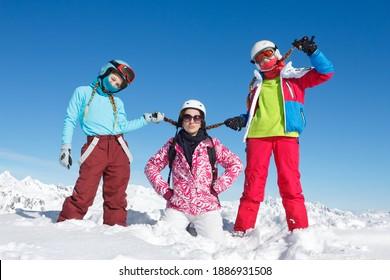 jeunes filles colorées posant dans la neige fraîche sur les pistes de ski et le ciel bleu