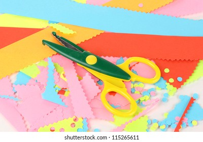 Colorful zigzag scissors on color paper background