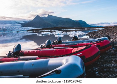 Colorful Zodiac boats on the beach coast of black sand volcanic rock stones in glacier lagoon Fjallsarlon mountains and glacier lagoon on the background icebergs floating water reflection