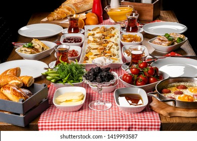 Colorful,fresh,organic,traditional village Turkish Breakfast at the wooden table on fabric table cloth.Used copper egg pan,ceramic casserole and bamboo bowls.Close up taken,top view