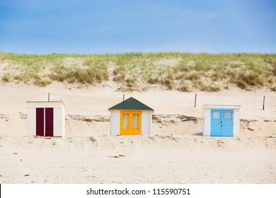 Colorfull Dutch houses on the beach with blue sky. Texel, Holland