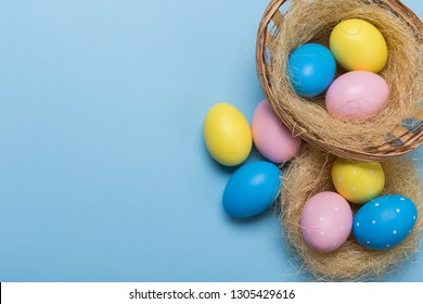 Colorfull easter eggs in nest on blue pastel color background with space.