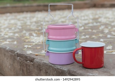 colorfull enamelled tiffin food and red cup on floor have flower metal