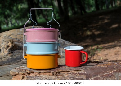 colorfull enamelled tiffin food and red cup on wood metal