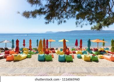 Colorfull umbrellas and lounge chairs at the beach of Agia Eleni, Skiathos island, Sporades, Greece