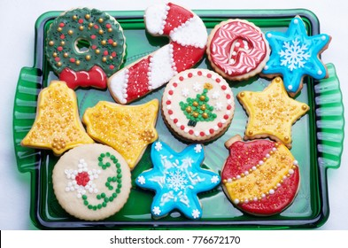 Colorfully Decorated Out Out Christmas Cookies, Homemade And On Green Glass Tray