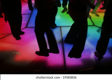 Colorfully lit dance floor, with human silhouettes in motion, dancing