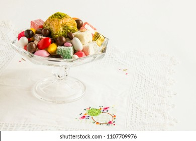 Colorful,Traditional Turkish candies (badem,akide)and chocolates designed around one slice of baklava in the glass candy bowl.Used handmade lace cloth on white surface.Sugar or any feast celebrate.
