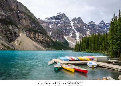 Colorfuly rental canoes resting on a dock at Moraine Lake in Banff National Park, Alberta, Canada, which is famous for its beautiful turquoise water.