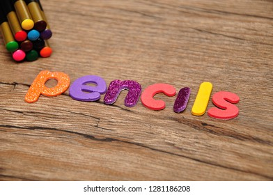 Coloring pencils with the word pencils on a wooden background