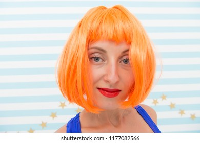Coloring and treatment professional salon service. Wig bright artificial hair looks unnatural. Hair revival procedure advice. Cosmetics for care and revival. Lady red ginger wig and make up close up.