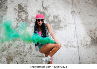 Coloring the world. Playful young women holding smoke bomb and smiling while posing against the concrete wall