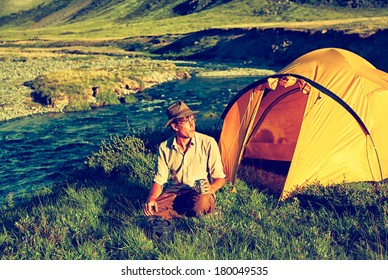 Colorized vintage outdoor portrait of tourist in Altai camp sitting near the river and drinking tea