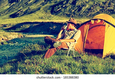 Colorized vintage outdoor portrait of tourist in Altai camp sitting in the chair near the sriver
