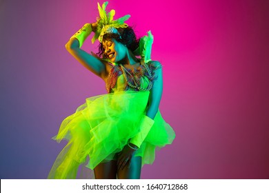 Colors. Beautiful young woman in carnival, stylish masquerade costume with feathers dancing on gradient background in neon light. Concept of holidays celebration, festive time, dance, party, having