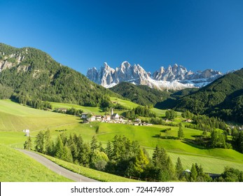 Colors of Dolomites. funes view of the valley, Puez-Odle in autumn. at sunset holy magdalena. View of odle mountain. Santa Maddalena, Tyrol, Italy. Green grass, mountains and blue sky. Summer