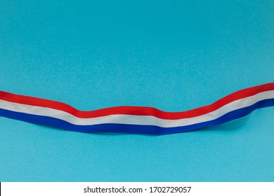 The colors of the Dutch flag, red white and blue on a ribbon. Blue background with room for copy.