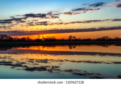 The colors of the rising sun and clouds are reflected on a country pond with a fence surrounding it.