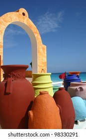 colors set off local pottery under an arch by the sea in Cancun, in Yucatan, Mexico