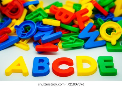 Colorul plastic letters spelling text ABCDE with pile of colorful letters background