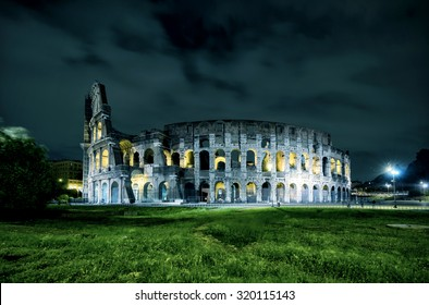 Colosseum or Coliseum at night, Rome, Italy. Roman Colosseum is one of the main travel attractions of Rome. Night view of Colosseum in illumination lights. Panorama of illuminated Colosseum at dusk.