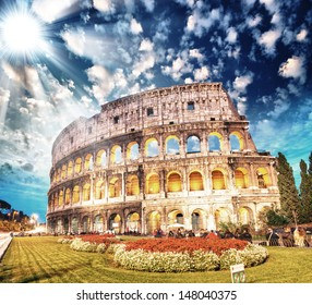 Colosseum - Rome. Sunset view with surrounding grass and park.