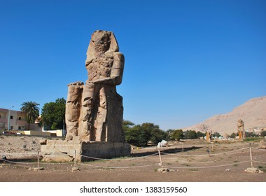The Colossus of Memnon, massive stone statue of Pharaoh Amenhotep III in West Coast of Luxor, Egypt