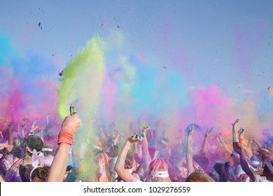 colour burst of powder with arms in the air and people