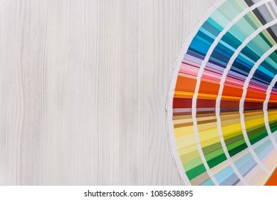 Colour guide on light wooden background, top view