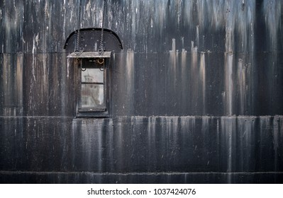 Colour image of a buildings reflection in a window that is on the side of a rusty ship
