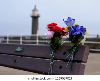 Colour image of floral tributes left on a bench at Whitby Pier.