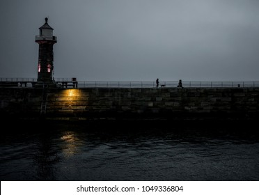 Colour image of a lighthouse on a pier in Whitby UK. Taken at dusk with people walking along.