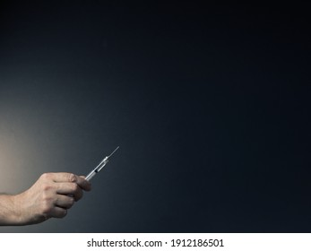 Colour image of man's hand holding syringe upwards in fingertips with dramatic lighting and text space to right