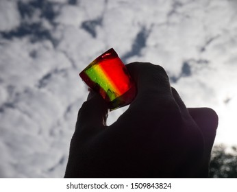 Colour image of a rainbow striped cube of jelly (jello) held between fingers against a blue sky with white fluffy clouds, shot from below so the sun shines through and lights up the jelly
