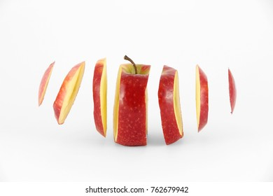 A colour image of a red apple that has been sliced and the slices are floating thru the air. The image was shot using a white background.